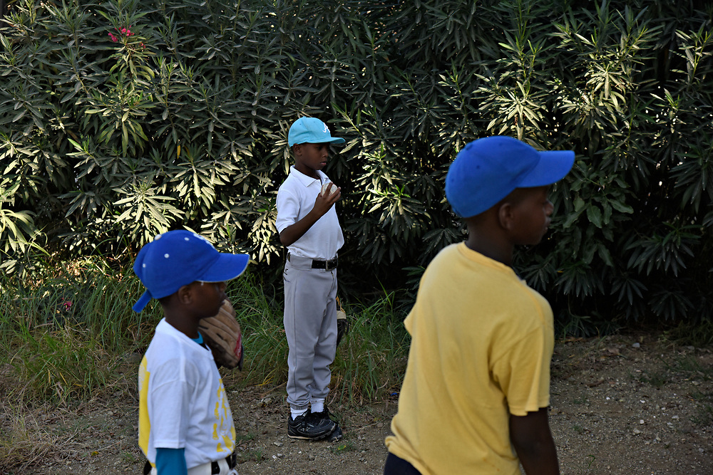 "WILLEMSTAD, CURACAO - DECEMBER 10, 2014: Members of the Marchena Hardware 7-9 year old Liga Vruminga team, which translates to ""league of little ants,"" play behind the dugout until the older boys are off the field. (photo by Melissa Lyttle)"