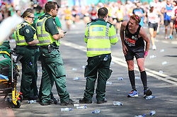 © Licensed to London News Pictures. 22/04/2018. London, UK. A man with cramp is attended to by London MAbulance workers during the 2018 London Marathon which is being run in unusually warm temperatures for April. This years event is being started by HRH Queen Elizabeth II. Photo credit: Tom Nicholson/LNP