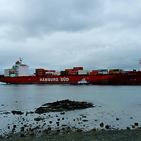 Container ship with the help of 2 tug boats negotiate Duneidn harbour