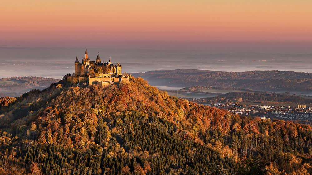 Blick auf die Burg Hohenzollern vom Zeller Horn bei Sonnenaufgang.  In der Schwäbischen Alb thront die weithin sichtbare Burg Hohenzollern auf einem markanten Bergkegel. Sie ist Stammsitz eines der berühmtesten süddeutschen Grafengeschlechter, aus dem u. a. das Haus Preußen erwuchs.