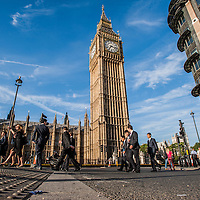 Business people cross  the street under the Big Ben tower in London on July 30, 2014.