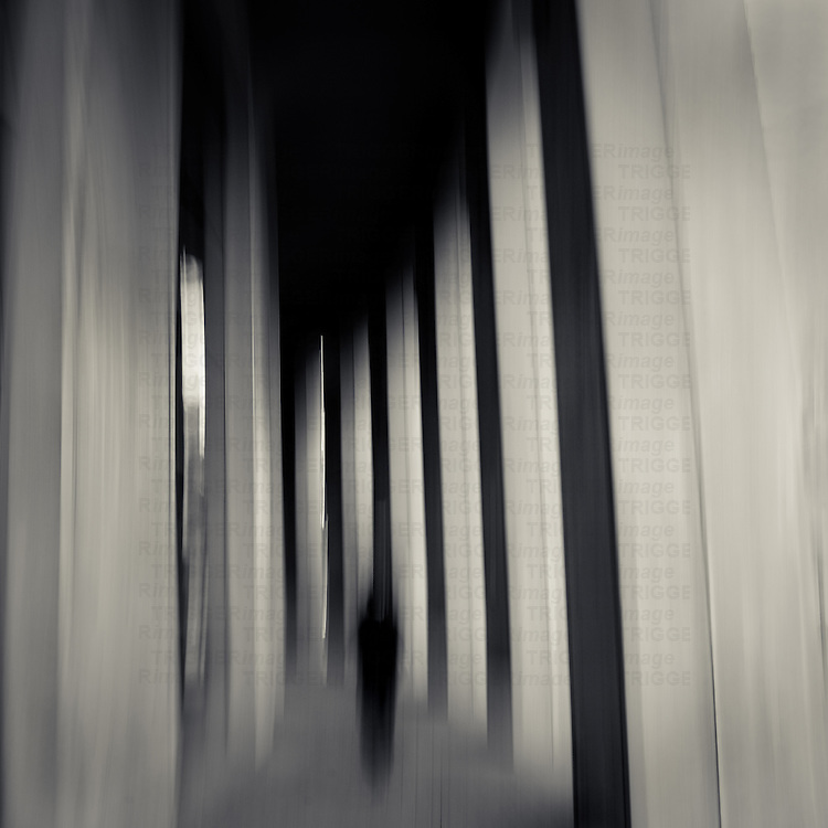 A blurred man walking through colums at the Vancouver Public Library with intentional camera movement.