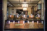 Hiroko Kimura stands at the counter of Tamaiya senbei rice cracker store in Shimokitazawa, Setagaya Ward, Tokyo, Japan..Photographer: Robert Gilhooly