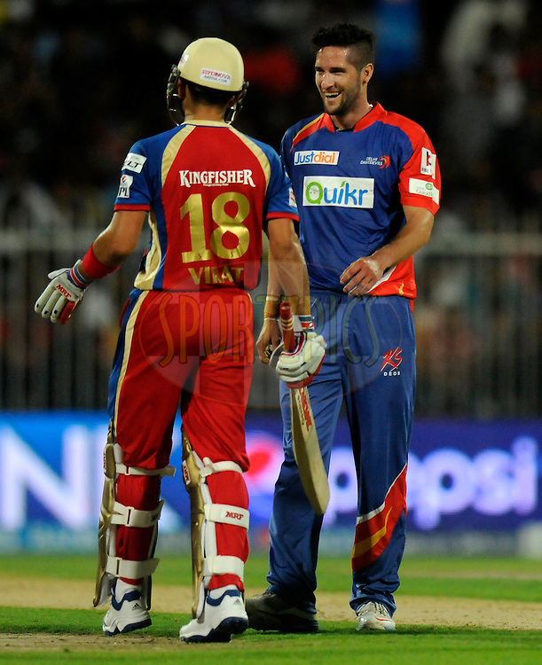 Wayne Parnell of the Delhi Daredevils shares a lighter moment with Virat Kohli captain of the Royal Challengers Bangalore during match 2 of the Pepsi Indian Premier League Season 7 between the Delhi Daredevils and The Royal Challengers Bangalore held at the Sharjah Cricket Stadium, Sharjah, United Arab Emirates on the 17th April 2014<br /> <br /> Photo by Pal Pillai / IPL / SPORTZPICS