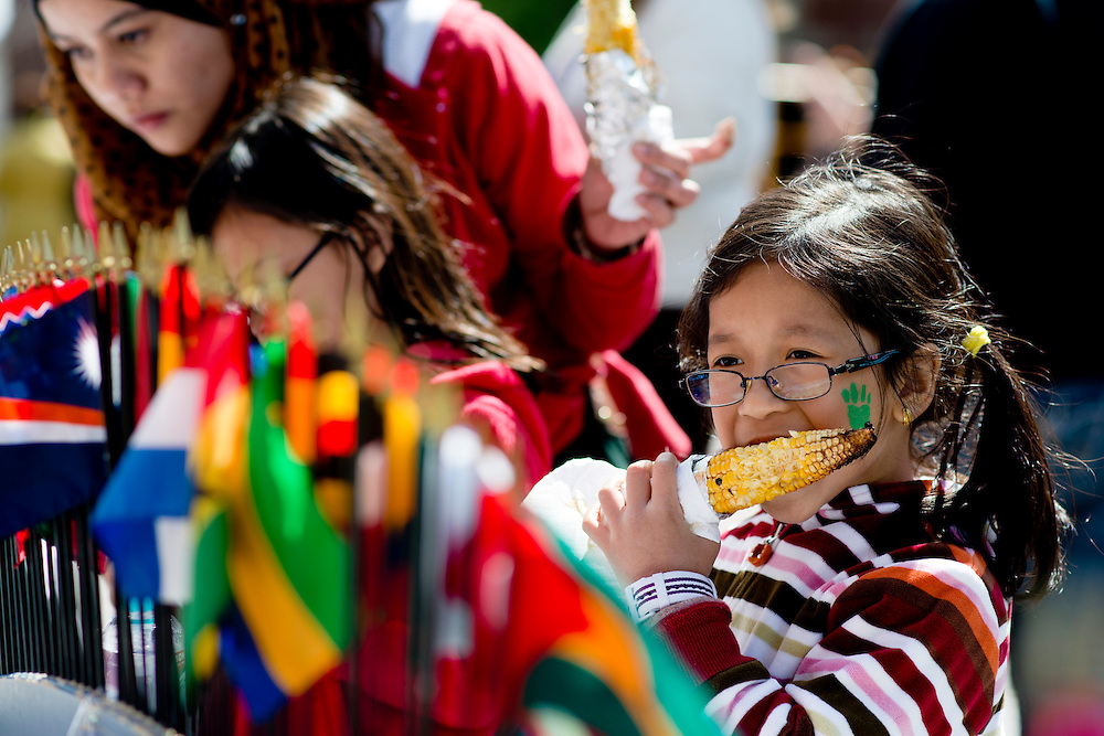 "Nurul Sarah Daus (8) eats some grilled corn made by the Japanese Student Association while she looks at all the different countries flags at a booth set up for the International Street Fair Saturday, April 20, 2013. The International Street Fair was held on Court Street from 11 a.m. to 5 p.m. during the last day of Ohio University's annual ""International Week."""