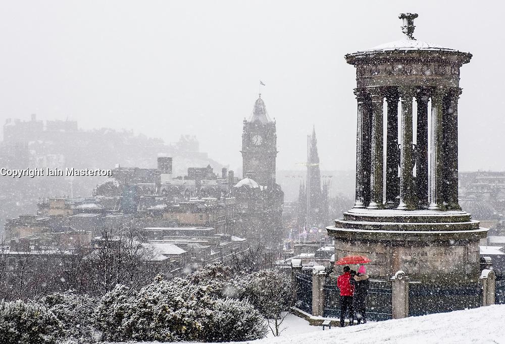 Snow falls on city of Edinburgh in December. Skyline view of city from Calton Hill, Scotland, UK.