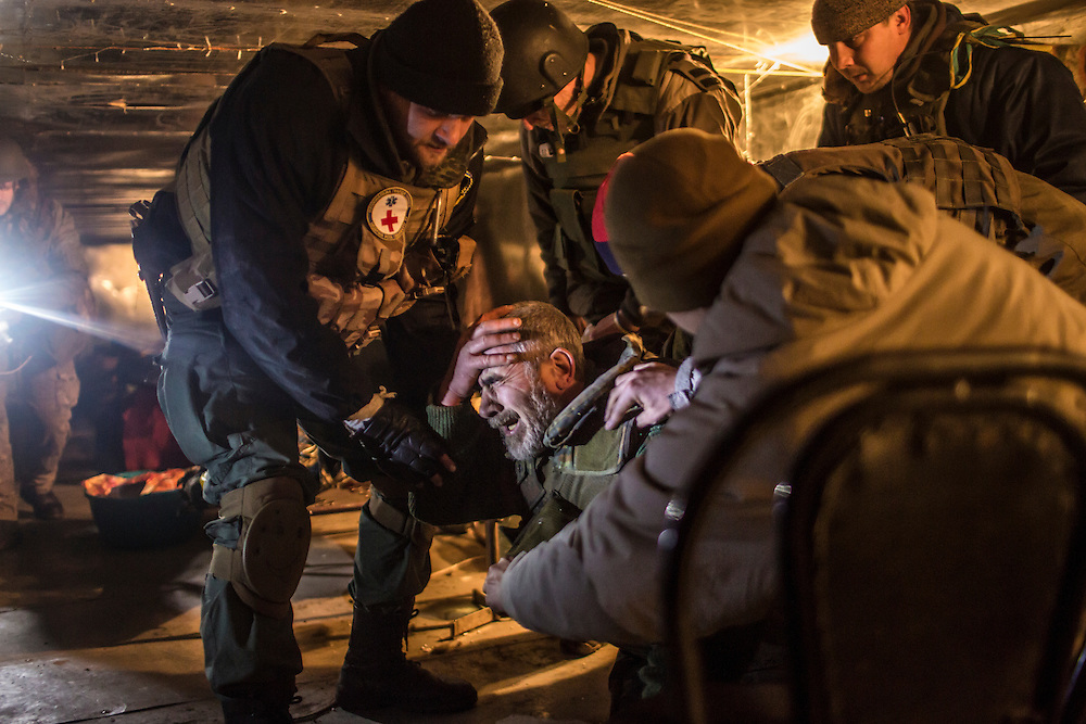 An ambulance driver named Tariel, a Ukrainian Army medic, collapses in pain after receiving a shrapnel wound to the arm during shelling near a medical treatment point for Ukrainian fighters on February 8, 2015 in Debaltseve, Ukraine. Fighting between pro-Russia rebels and Ukrainian forces there over the past two weeks has dealt steady casualties to Ukrainian fighters and civilians.