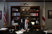 """MONTGOMERY, AL – JUNE 25, 2015: <br /> Alabama Department of Corrections Commissioner Jeff Dunn works in his Montgomery office. Dunn was appointed to his position by Governor Robert Bentley on April 1, 2015. <br /> The Alabama Justice Reinvestment Act (SB67), more commonly referred to as the Criminal Justice Reform Act, has received bi-partison support in the state of Alabama where aging prison infrastructure has not kept up with the demands of a rising inmate population. With prison facilities averaging 184% capacity, the bill attempts to alleviate overcrowding through a combination of sentencing reform and the expansion of supervised probation and local community corrections programs.<br /> As of June 2015, the Alabama Department of Corrections housed 24,511 inmates across 28 correctional facilities, representing a 470% increase in the inmate population since 1978. Although additions have been built at most facilities to accommodate more beds, infrastructure remains largely unchanged, limiting restrooms and kitchens to their original design capacity. In most facilities breakfast starts at 3:30 am, with lunch following at 9:30. """"You basically have to keep the kitchen going all day, just get everybody through,"""" said Dewayne Estes, warden at St. Claire Correctional Facility in Springville, Alabama. <br /> CREDIT: Bob Miller for The Daily Signal"""
