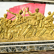 A large gold frieze on the Independence Monument in downtown Sam Neua (also spelled Samneua, Xamneua and Xam Neua) in northeastern Laos. It depicts contribution of international socialism to the Lao struggle for independence, with soldiers, farmers, and workers in gold against the backdrop of the Lao flag.