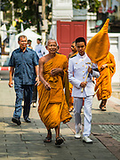 14 DECEMBER 2015 - BANGKOK, THAILAND: Senior Buddhist monks walk into Wat Bowon Niwet with their attendants for the funeral of Supreme Patriarch at Wat Bowon Niwet in Bangkok. Somdet Phra Nyanasamvara, who headed Thailand's order of Buddhist monks for more than two decades and was known as the Supreme Patriarch, died Oct. 24, 2013, at a hospital in Bangkok. He was 100. He was ordained as a Buddhist monk in 1933 and appointed as the Supreme Patriarch in 1989. He was the spiritual advisor to Bhumibol Adulyadej, the King of Thailand when the King served as a monk in 1956. His funeral, which will take three days,   Dec. 15-17, will be attended by thousands of Thais and most of the Royal Family. Buddhist clergy from around the world are expected to attend.       PHOTO BY JACK KURTZ