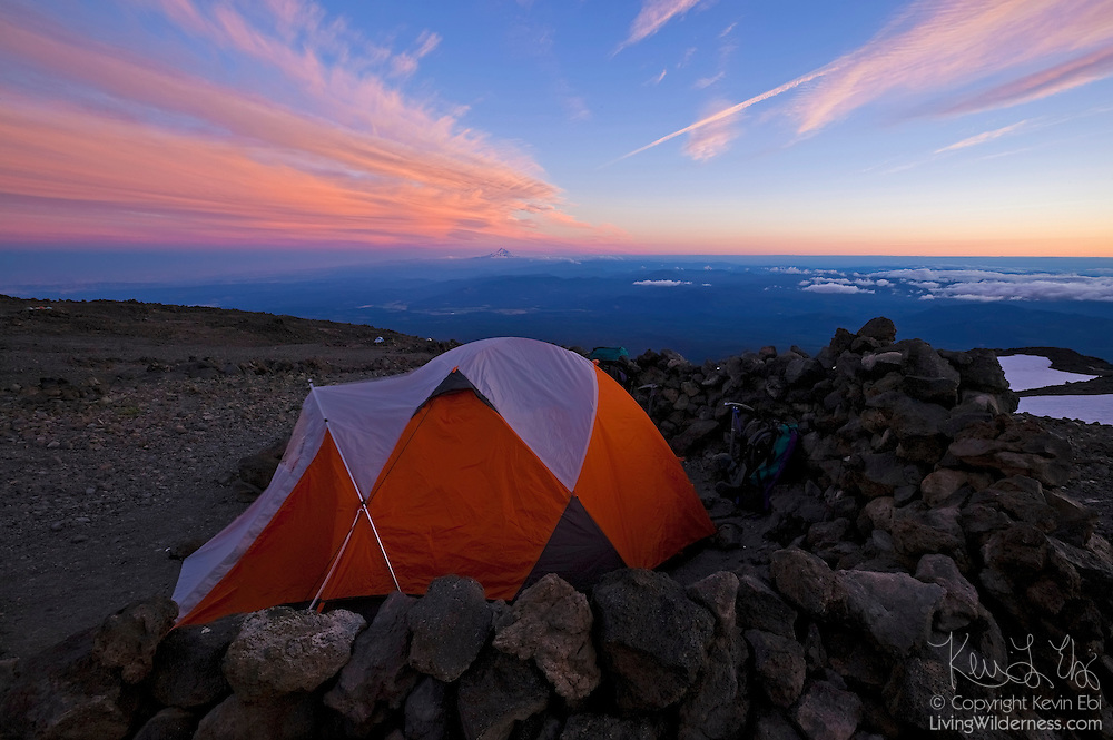 Climbers planning to climb Mount Adams in Washington typically camp at the Lunch Counter, located at about 9,000 feet elevation. Mount Hood in Oregon, also part of the Cascade mountain range, is visible on the horizon.
