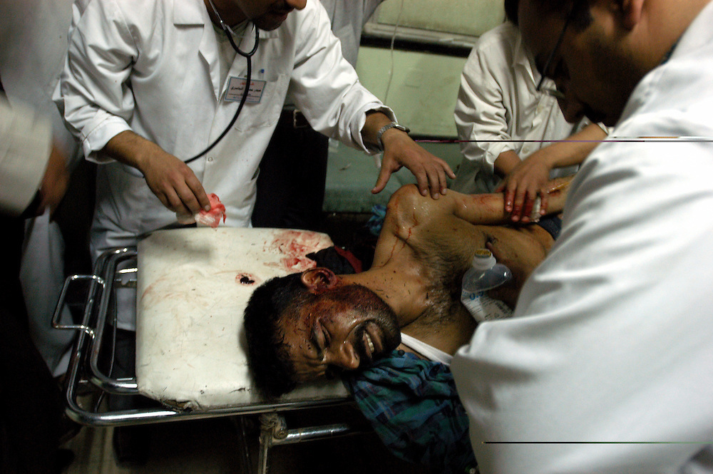 Doctors examine a man with multiple gun shot wounds at the al-Kadisia Hospital emergency room in Thora City, formerly known as Saddam City. The neighborhood is a vast slum of 3 million Shiite Muslims, long oppressed and marginalized by Saddam's regime. The area is a hotbed for the violence and insecurity that has thrived with the absence of authority in the country..Baghdad, Iraq. 06 May 2003..Photo © J.B. Russell