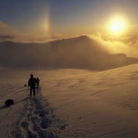 USA, Alaska, Denali National Park, (MR) Expedition descends Kahiltna Glacier at sunset at 11,000' during Mount McKinley climb