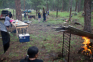A week before the event, Alexis' family builds a camp for the upcoming dance. The men unload railroad ties off the bed of a pickup truck, dig holes in the earth, insert the logs into the soil and string barbwire forming a circle with open air and an entrance to the east.  The compound later will be covered with cottonwood and willows.