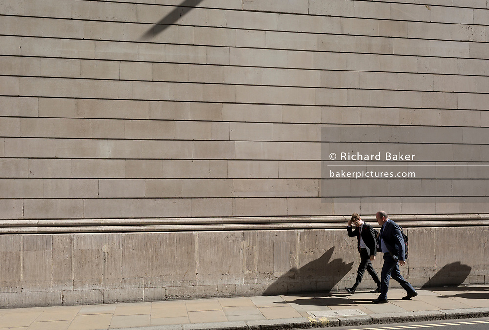Two businessmen walk beneath the high outer walls of the Bank of England in the City of London, the capital's financial district, on 25th March 2019, in London, England.