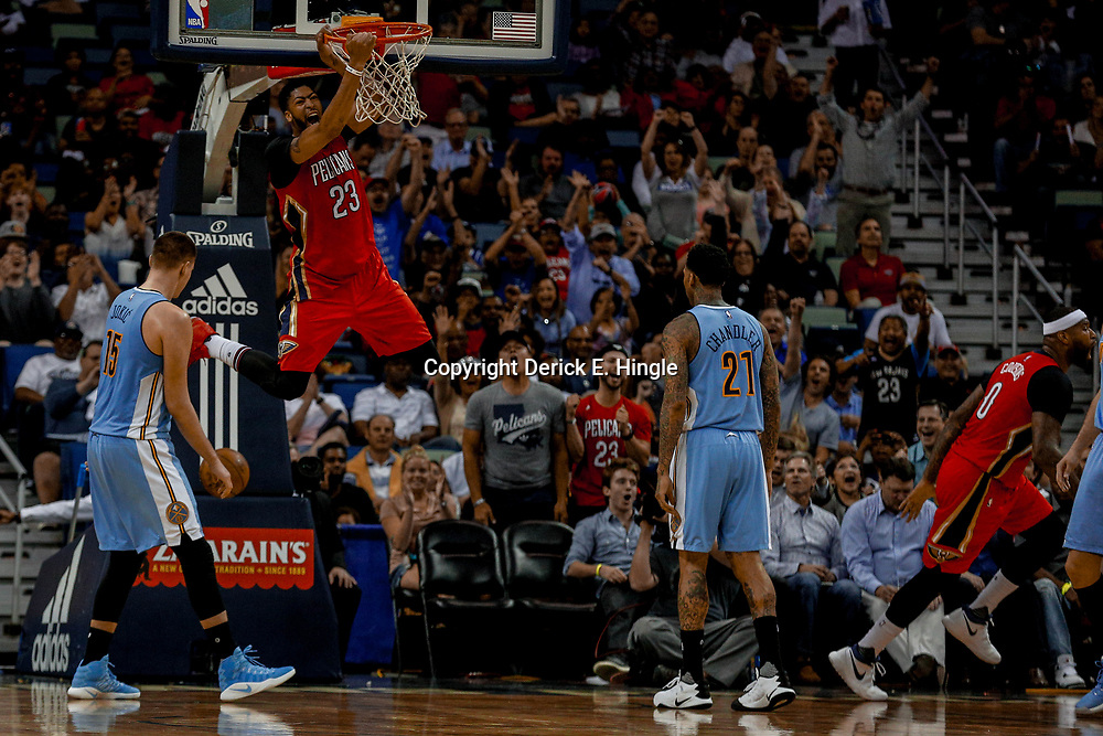 Apr 4, 2017; New Orleans, LA, USA; New Orleans Pelicans forward DeMarcus Cousins (0) celebrates as forward Anthony Davis (23) dunks over Denver Nuggets forward Nikola Jokic (15) during the second quarter of a game at the Smoothie King Center. Mandatory Credit: Derick E. Hingle-USA TODAY Sports