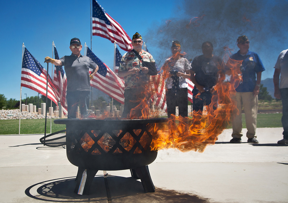 mkb061417a/metro/Marla Brose --  A fire burns brightly as five worn American flags are retired during a ceremony at the New Mexico Veterans Memorial, Wednesday, June 14, 2017, in Albuquerque, N.M. Everyone at the ceremony participated in cutting each flag, stripe by stripe, and keeping the stars together. Then the pieces were thrown into a fire. One of the speakers at the ceremony, Diana Wong, said that people can take their worn flags to a box outside the visitors center at the New Mexico Veterans Memorial to have them burned with dignity. Information about flag education programs are also available at the center. (Marla Brose/Albuquerque Journal)