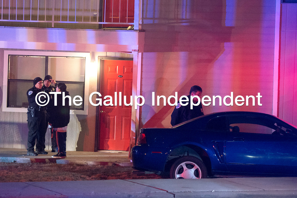 Gallup Police Officers speak with the driver of a vehicle and investigate the scene of a singe car accident that drove off the road near Cliffside Apartments Wednesday night.