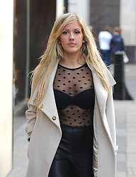 Brit Awards winner Ellie Goulding wearing a cream coat, see-through polka-dot top/ leather trousers and black boots out shopping at H&M in Oxford Street, London, UK. 25/02/2014<br />