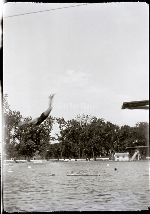 swimming pool with person diving from diving board 1920s