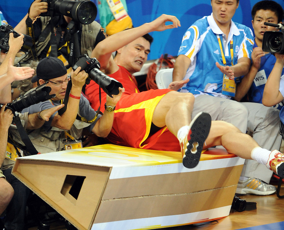 2008 OLYMPIC GAMES  MEN'S BASKETBALL - USA VS. CHINA  - 081008 - China's Yao Ming crashes into a bank of photographers along the baseline  during the USA's rout in the opening round, 101-70.