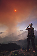 Nuclear Winter test fire: brown smoke rises from smoldering brush fires, deliberately started to study the potential climatic effects of a nuclear war. The nuclear winter theory predicts that smoke from fires burning after a nuclear war would block sunlight, causing a rapid drop in temperature that would trigger serious ecological disturbance. The test burn took place in December 1986 on 500 acres of brush in Lodi Canyon, Los Angeles. Dripping napalm from a helicopter ignited the fire. Ground-based temperature sensors were used to study soil erosion. Various airborne experiments included smoke sampling & high-altitude infrared imaging from a converted U-2 spy plane.