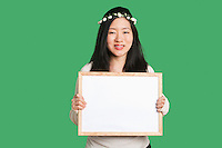 Portrait of a young woman holding a blank whiteboard over green background
