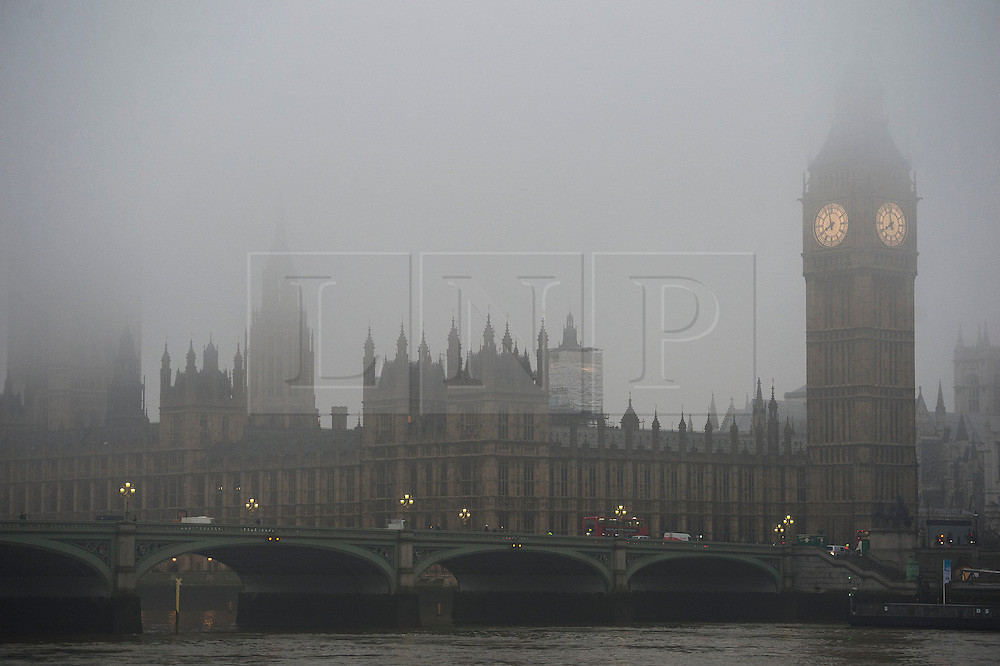 © London News Pictures. 21/01/2014. London, UK.  Traffic passing over Westminster Bridge in front of the Houses of Parliament in Westminster shrouded in fog early morning in central London on January 21, 2014. Photo credit: Ben Cawthra/LNP