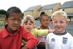 Four children playing on their Housing Association estate; Halifax; Yorkshire UK