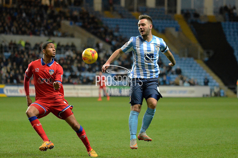 Oldham Athletic midfielder Timothee Dieng keeps an eye on Coventry City striker Adam Armstrong during the Sky Bet League 1 match between Coventry City and Oldham Athletic at the Ricoh Arena, Coventry, England on 19 December 2015. Photo by Alan Franklin.