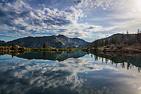 A mirrored reflection of the sky in the calm waters of Cecret Lake, high in Little Cottonwood Canyon at Albion Basin.
