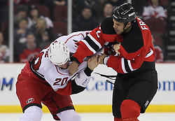 Feb 16; Newark, NJ, USA; Carolina Hurricanes right wing Troy Bodie (20) and New Jersey Devils defenseman Mark Fraser (2) fight during the first period at the Prudential Center.