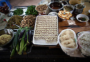 A table in a restaurant is laden with wonton noodles and the ingredients for wonton soup in Chongqing.
