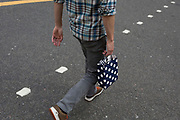A man carries a small bag featuring spots, with the dots from a road crossing, on 29th August 2018, in London, England.