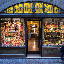 Bergamo, Italy - A child runs towards a toy store in Via Gombino, the main street of the historical centre of Città Alta, Upper Bergamo
