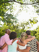 Two couples standing arm in arm in garden back view