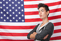 Portrait of confident young man with arms crossed standing against American flag