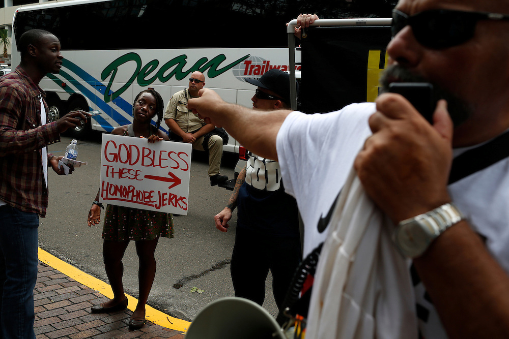 A woman holds a sign in protest against a group that refer to themself as The Official Street Preachers on the streets of Tampa during the  2012 Republican National Convention on August 29, 2012.
