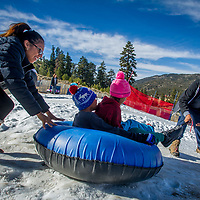 Diana Martinez of Los Angeles County gives a push as Jesus Carrasco pulls to start kids Destiny and Damien Canales down the slope as visitors enjoy the newly-made snow during opening day at Big Bear Snowplay in Big Bear City, Sunday, Nov. 19, 2017. The local temperatures from the night time mid 20's to mid 50's in the day have made for Big Bear Snowplay to make from 6 inches to 2 1/2 foot base. Snowplay will continue to make new snow every night along with other mountain recreation areas and resorts. (Eric Reed/For The OC Register/SCNG)