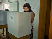 08 NOVEMBER 2015 - YANGON, MYANMAR: A woman in a voting booth marks her ballot at her voting place in a public school in central Yangon. The citizens of Myanmar went to the polls Sunday to vote in the most democratic elections since 1990. The National League for Democracy, (NLD) the party of Aung San Suu Kyi is widely expected to get the most votes in the election, but it is not certain if they will get enough votes to secure an outright victory. The polls opened at 6AM. In Yangon, some voters started lining up at 4AM and lines were reported to long in many polling stations in Myanmar's largest city.      PHOTO BY JACK KURTZ