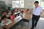 QIANNAN, CHINA - MAY 31: (CHINA OUT) <br /> <br /> Six-pupil School In Mountain Of Qiannan<br /> <br /> The only teacher Wu Guoxian teaches pupils at Gugang primary school in a mountain in Longli County on May 31, 2016 in Qiannan Buyei and Miao Autonomous Prefecture, Guizhou Province of China. Gugang primary school with only one teacher and six students was located in the mountain where the traffic was blocked in Qiannan. 50-year-old Wu Guoxian had been teaching in this school for 33 years and taught over 1,000 students. More and more people went out of the village to work in the cities leaving their children and the old in the mountain. Five under-school-age kids whose parents left for work also stayed at the school.<br /> ©Exclusivepix Media
