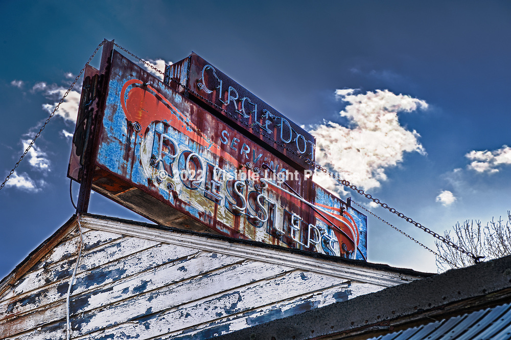 Aging neon sign over an abandoned hot dog stand