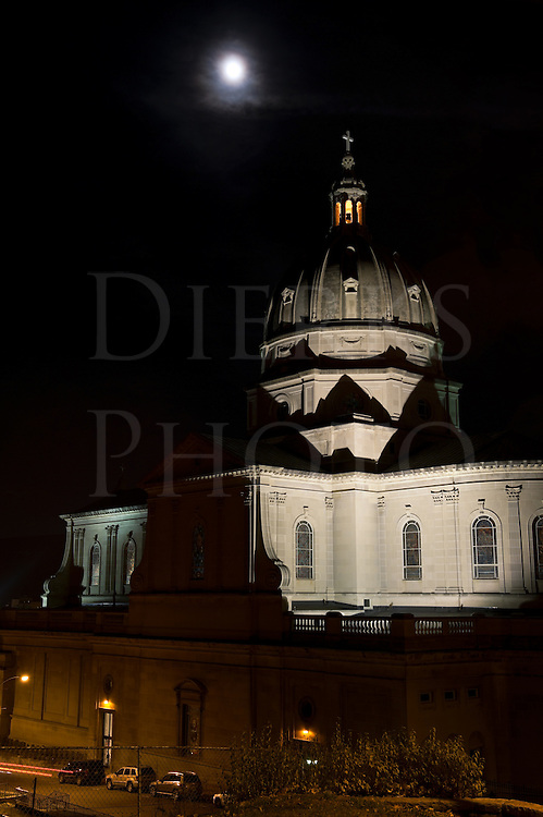 Cathedral church dome under full moon, photographed at night with top tower lit, Altoona, PA, USA.