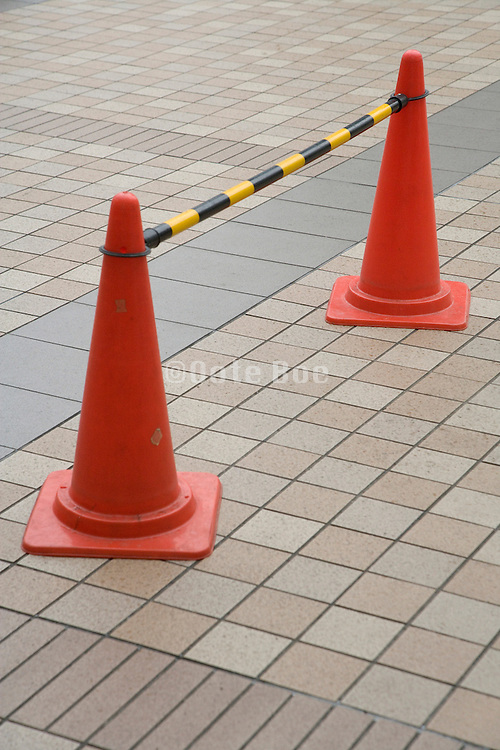 two cones with bar blocking part of a pedestrian walkway