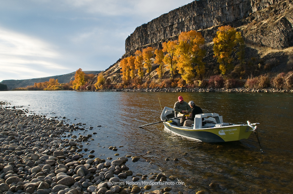 Fly fisherman in a drift boat search a fly box for the right pattern to catch trout during an autumn evening on the South Fork of the Snake River, Idaho.