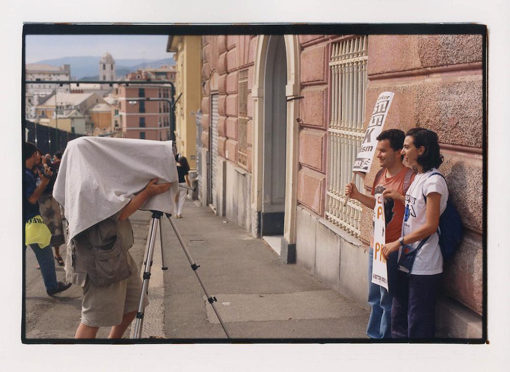 Proteste contro il summit del G8, Genova luglio 2001. 19 luglio, corteo dei Migranti. Due manifestanti posano davanti all'obiettivo di una macchina fotografica da studio durante la manifestazione. La massiva partecipazione della società civile italiana e internazionale alle manifestazioni contro il G8 attira l'attenzione di n grande numero di intellettuali e creativi che partecipano agli eventi nei modi più diversi.
