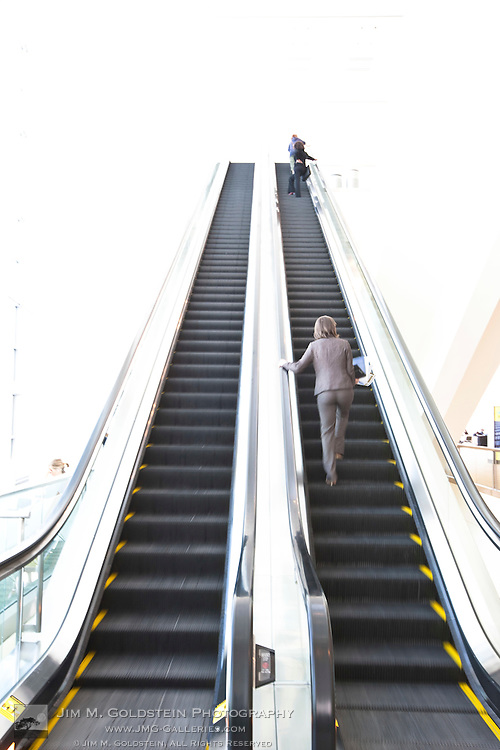 A few people ride up an escalator in Moscone West conference center - San Francisco, California