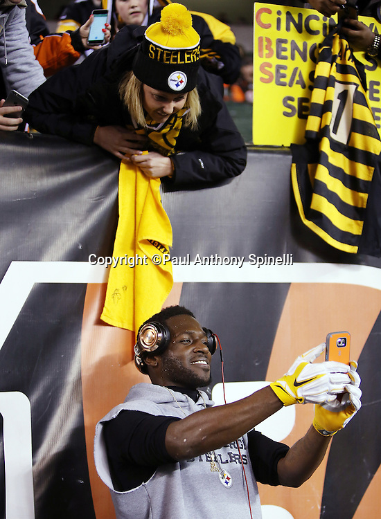 Pittsburgh Steelers wide receiver Antonio Brown (84) takes a selfie photograph of himself and a fan for a fan before the NFL AFC Wild Card playoff football game against the Cincinnati Bengals on Saturday, Jan. 9, 2016 in Cincinnati. The Steelers won the game 18-16. (©Paul Anthony Spinelli)
