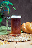 A mug of dark ale with bread and pretzels.