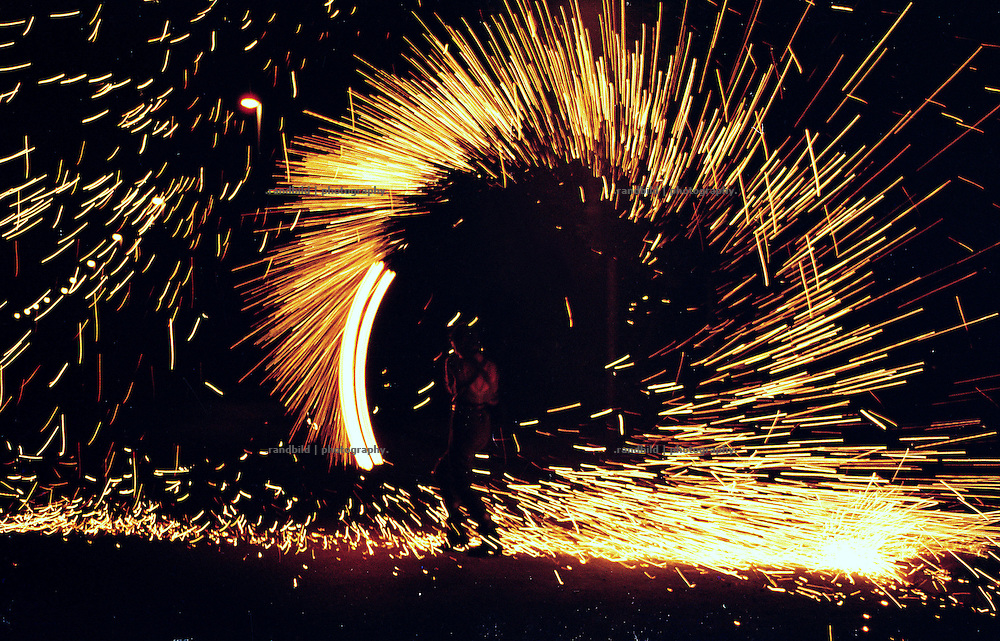 "..Eine Straßenkünstlerin schleudert eine Feuerkette. Eine feuershow im Rahmen des ""Grenzcamps"" 1999. An Artist rotate a chain with a burning bowl at the end."